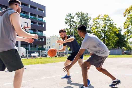 sport, leisure games and male friendship concept - group of men or friends playing street basketball