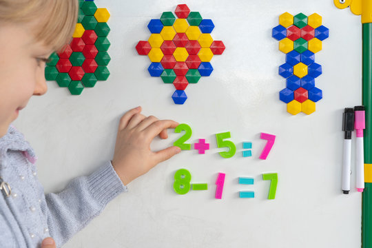 Little preschooler girl on magnetic interactive white borad is studying addition and subtraction in math lesson. Education School Preschool concept.
