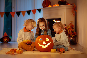 Kids carving pumpkin on Halloween. Trick or treat.