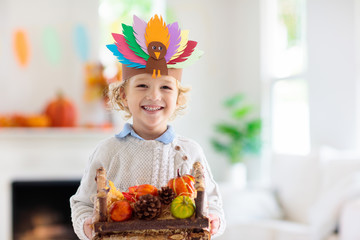 Child on Thanksgiving. Kid with autumn turkey hat. Wall mural