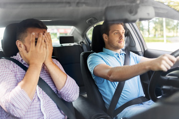 accident, emotion and fear concept - scared car driving school instructor and young male driver Fototapete