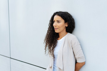 Young woman relaxing against a wall thinking