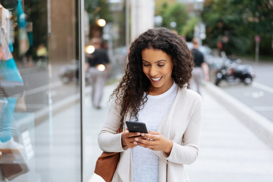 Happy young woman using her smartphone in town
