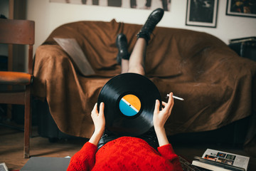 Retro woman listening music and holding a vinyl in her hands.