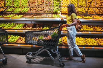 woman at grocery store market with shopping cart