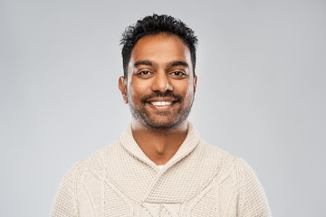 emotion, expression and people concept - smiling indian man in knitted woollen sweater over gray background
