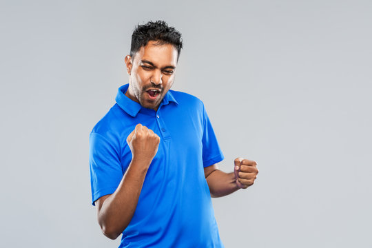 success, emotion and expression concept - happy young indian man celebrating victory over grey background