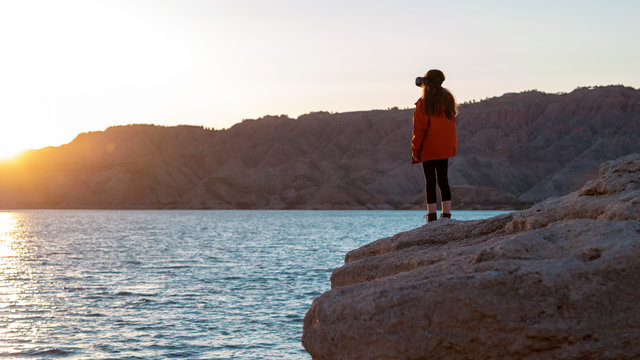Girl with a visual reality headset on looking over a lake with sunset