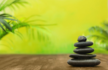 Fototapeta Table with stack of stones and blurred green leaves on background, space for text. Zen concept obraz