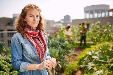 Friendly woman harvesting fresh vegetables from the rooftop greenhouse garden Fotoväggar