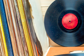 Vinyl record in front of a collection of albums, vintage process. Copy space for text