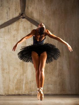 Young beautiful ballerina in black ballet tutu posing in dark studio