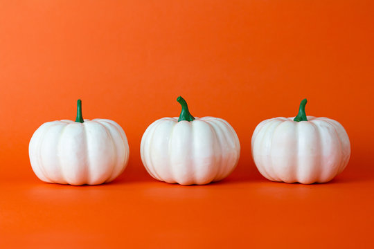 White pumpkin on orange background with copy space.