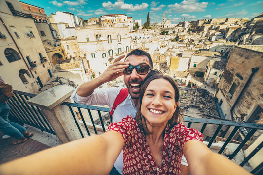 happy tourist travelling in south of italy, posing in a selfie photo in Matera, Basilicata, unesco site, capital of culture 2019