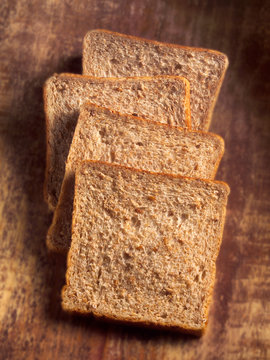 four slices of wholemeal bread against wood background