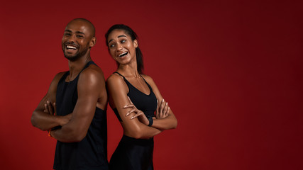 Staying healthy. Young and positive african fitness couple in sportswear looking at camera with smile while standing against red background
