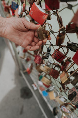 Close up of hand holding love padlock on bridge