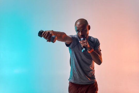 Perfect muscles. Strong young african man exercising with dumbbells while standing against colorful background