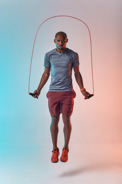 Staying fit. Full length of young african man in sport clothing skipping rope while exercising in studio against colorful background
