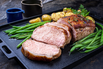 Traditional roasted dry aged veal tenderloin with beans and potatoes offered as closeup on a modern design cast iron tray