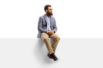 Fototapeta Bearded man sitting on a white banner and looking to the side