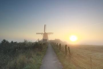 Wall Mural - misty gold sunrise behind Dutch windmill