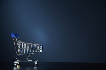 Shopping, sale or Black friday concept. Supermarket and discount. Shopping cart on grey background