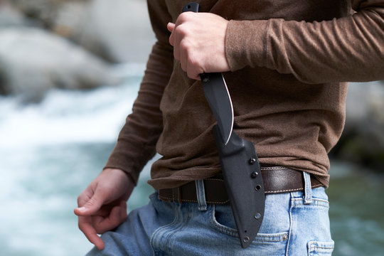 Man holding a tactical survival knife in the ready position outdoors in the wilderness.