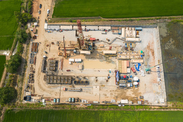 Wall Mural - Oil and gas land drilling rig onshore in the middle of a rice field aerial view from a drone