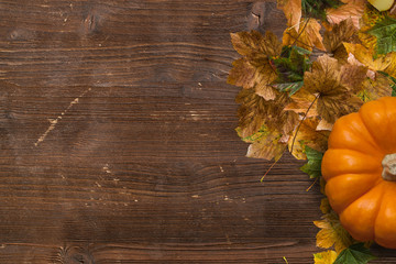 Fototapete - Autumn decoration with fallen leaves and pumpkin on wooden background
