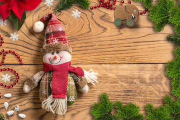 Christmas decoration and snowman rag doll on wooden background
