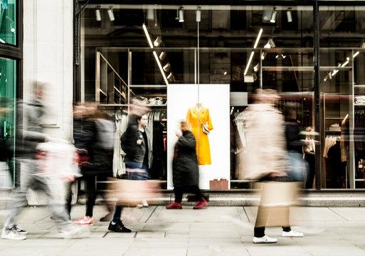 Motion blurred people walking past shop window