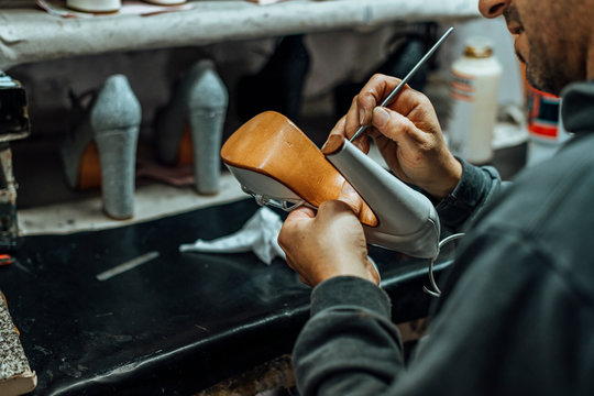 Hands of an old and experienced worker in the handmade footwear industry, performing cleaning and cosmetic tasks on products about to be finished.