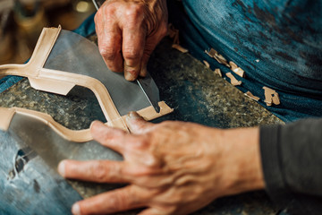 Hands of an old and experienced worker in the handmade shoe industry, performing assembly tasks with a blade, in his work section, refining the leather.