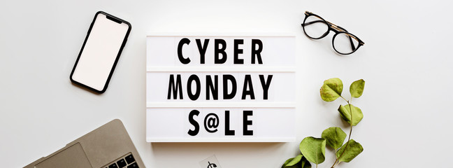 Creative promotion composition Cyber monday sale text on lightbox, laptop, mobile phone on white background. Horizontal banner for web design. Flat lay, top view, overhead, mockup, template