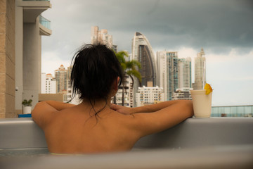 Beautiful lady is in jacuzzi. Dark hair woman is looking on a skyscrapers of the modern city. She is relaxing on the rooftop.