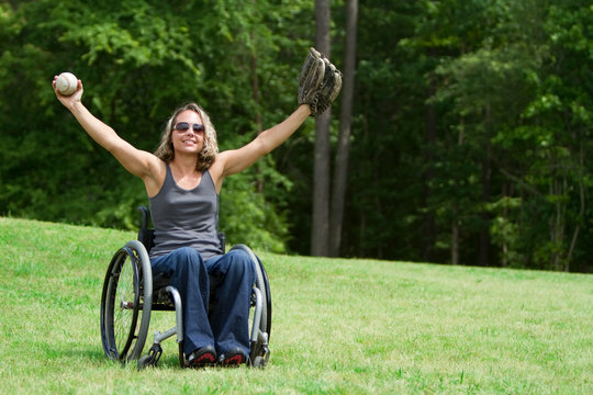 Woman in wheelchair playing catch at park