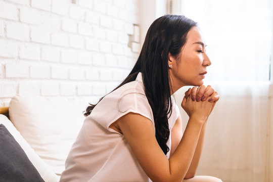 Mature Asian woman putting two hands together and praying at home. Joined and Clasped Hands. Spirituality and Religion concept