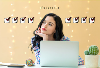 To do list with young woman using a laptop