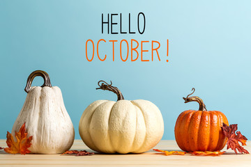 Hello October message with pumpkins on a blue background