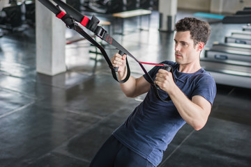 Athlete sporty man doing exercise with fitness trx straps to strengthen his abdominal muscle in gym