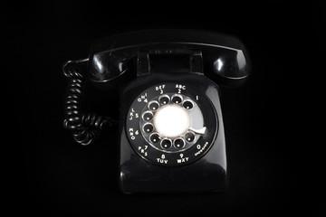 Fototapeta old fashioned  black rotary telephone on a black background