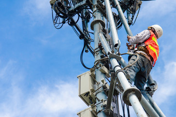 technician working on high telecommunication tower,worker wear Personal Protection Equipment for working high risk work,inspect and maintenance equipment on high tower.
