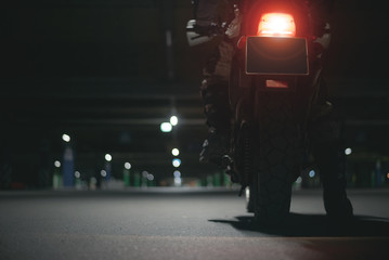 Motorbiker is sitting on his bike on a night parking area. Fototapete