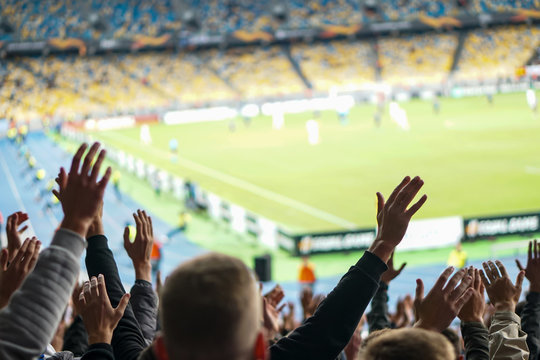 Football- soccer fans support their team and celebrate goal in full stadium with open air.