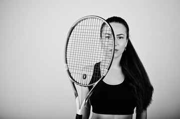 Black and white portrait of beautiful young woman player in sports clothes holding tennis racket while standing against white background.