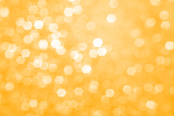 Christmas background. Blurred abstract background with sparkles, beautiful bokeh. Monochrome image in tones of Saffron color.