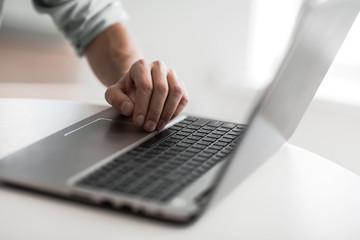 close up. a man uses a laptop.