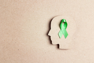 World mental health day concept. Green awareness ribbon with brain symbol on a brown background. Wall mural