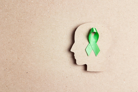 World mental health day concept. Green awareness ribbon with brain symbol on a brown background.